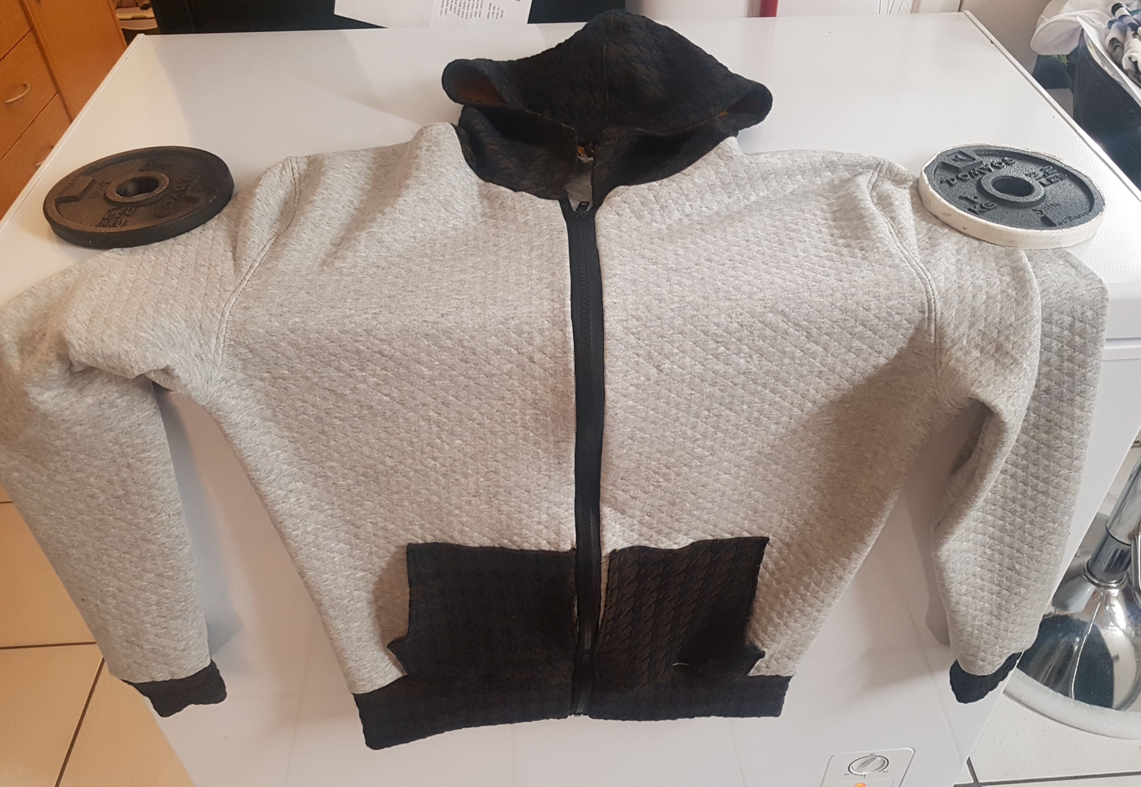 Huey hoodie laying on a washing machine, instead of on a human