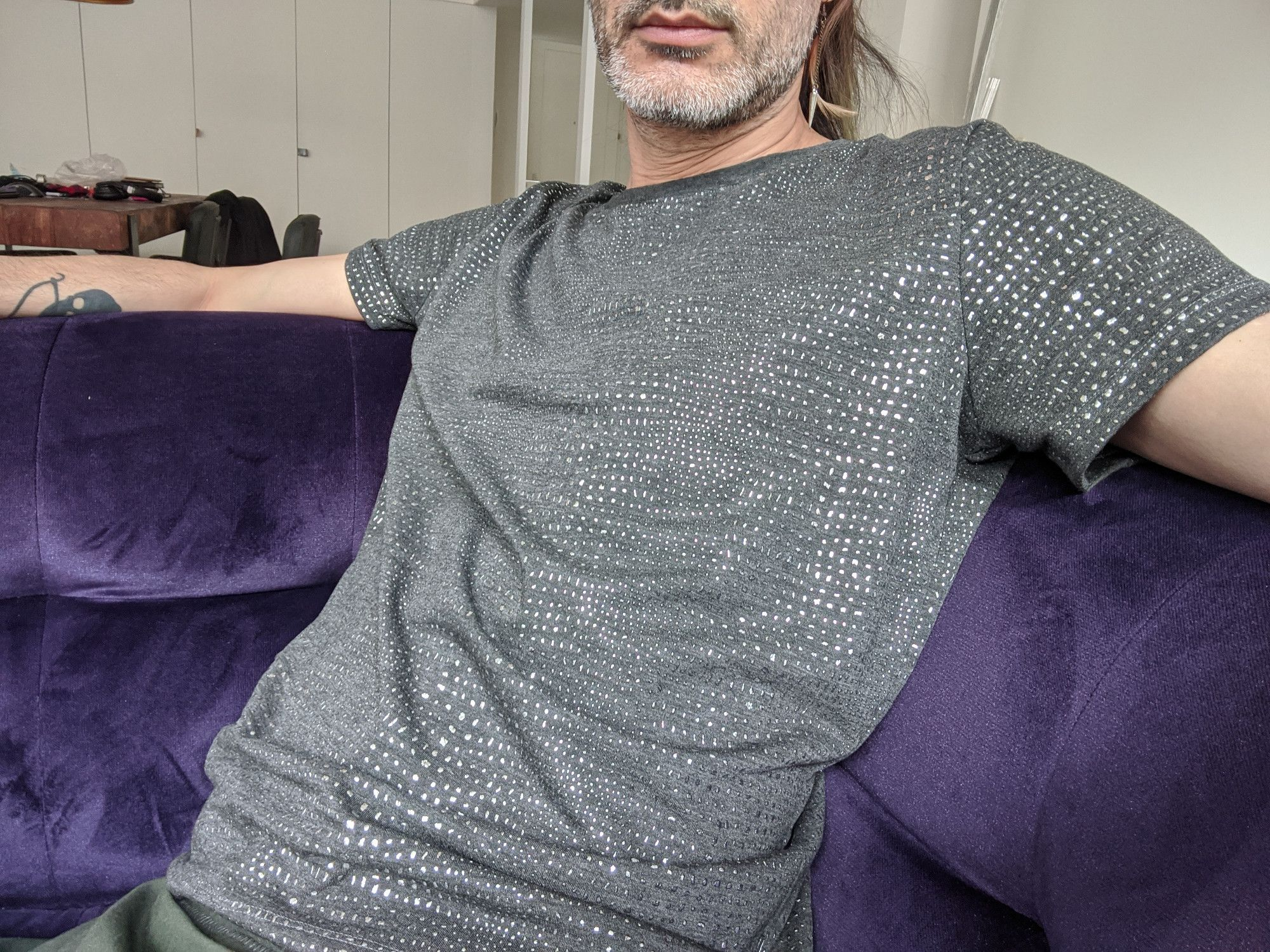 A man, seated on a purple couch and wearing a speckled grey Teagan T-Shirt.